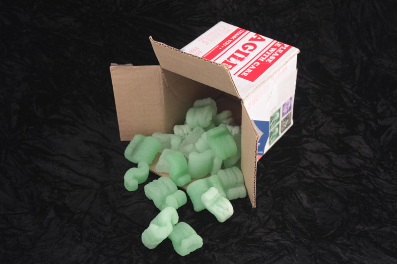Cardboard box with green cast glass packing peanuts