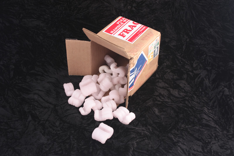 Cardboard box with pink cast glass packing peanuts