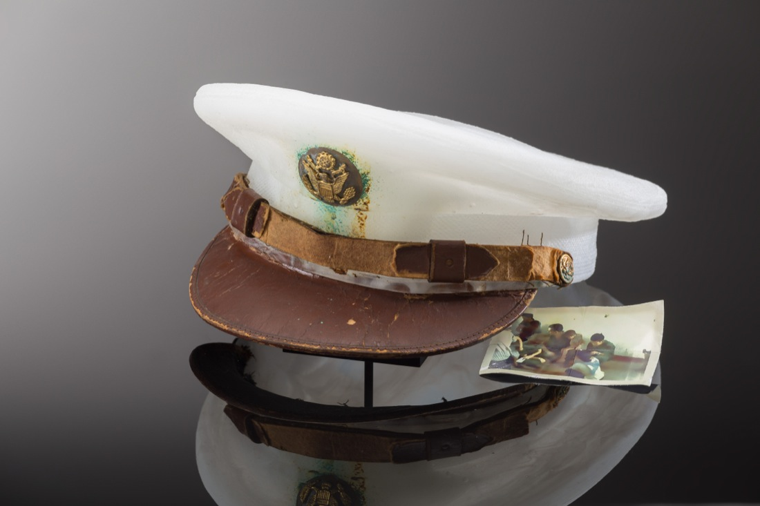Milky white cast glass hat with patina on the emblem and an old photograph